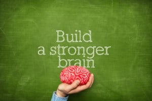 Build a stronger brain on green blackboard with hand holding artificial red brains